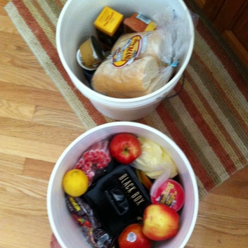 Food buckets with essentials: fruit, cookies, local bread, and plenty of wine.